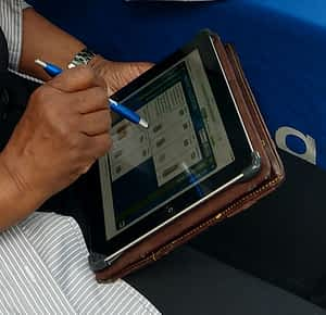 Brown hand holding a style marking a survey on a tablet